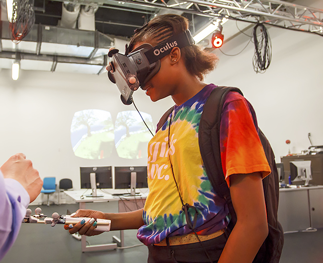 Dr. Ryan McMahan, assistant professor of computer science, led each girl through an immersive virtual reality experience. Donning a head-mounted 3-D display, the girls walked through a virtual house and used a hand-held controller to fly through a computer-generated world.