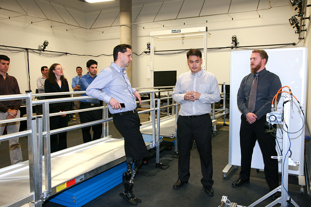 Before his lecture, Herr met with a handful of UT Dallas faculty and students. Here, engineering PhD students Hanqi Zhu (center) and Toby Elery describe the work they are doing in the Locomotor Control Systems Laboratory.